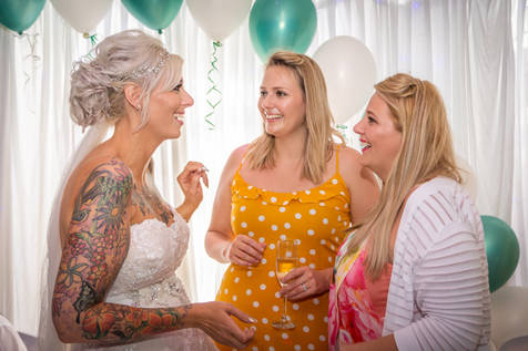The bride and bridesmaids are shown laughing happily at the wedding reception.