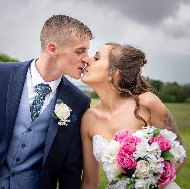 A just-married couple pause for a second before kissing. The bride wears a white, off the shoulder dress. The groom wears a blue suit.