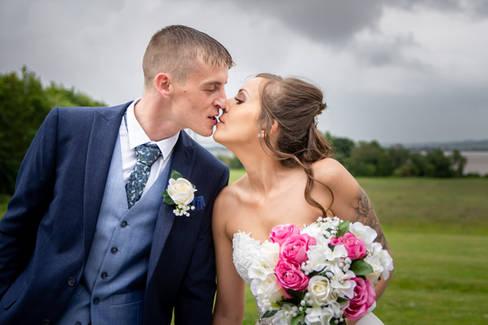 A newlywed bride and groom share a kiss outside the Hallmark Hotel near Hull.