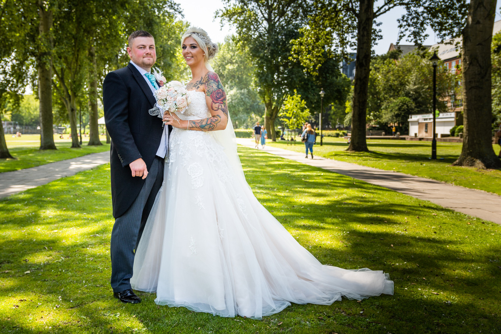 A wedding couple pose together between two avenues of trees in Queen's Gardens, Hull.