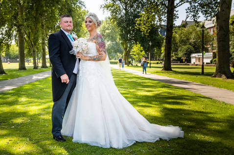 A newlywed bride and groom pose between two avenues of trees near Hull Guildhall.