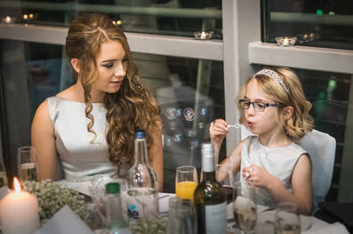 A bridesmaid and flower girl sit at the reception playing with a bubble wand at The Deep in Hull.