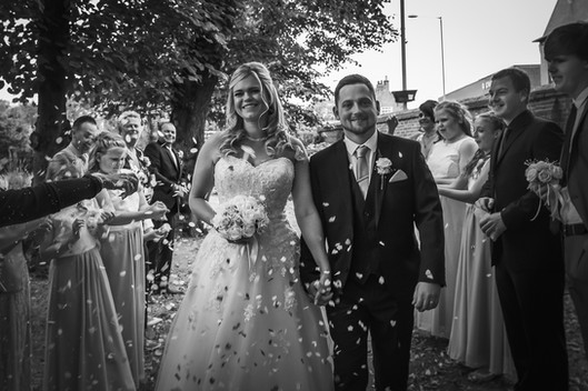 A newlywed couple walk between two rows of guests and are showered with confetti at Beverley Registry Office.