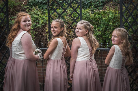 Four bridesmaids show the back detail of their dresses whilst looking back over their shoulders.