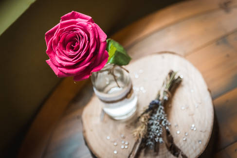 A detail shot of a table dressing featuring a single red rose and slice of wood at The Potting Shed, Beverley.