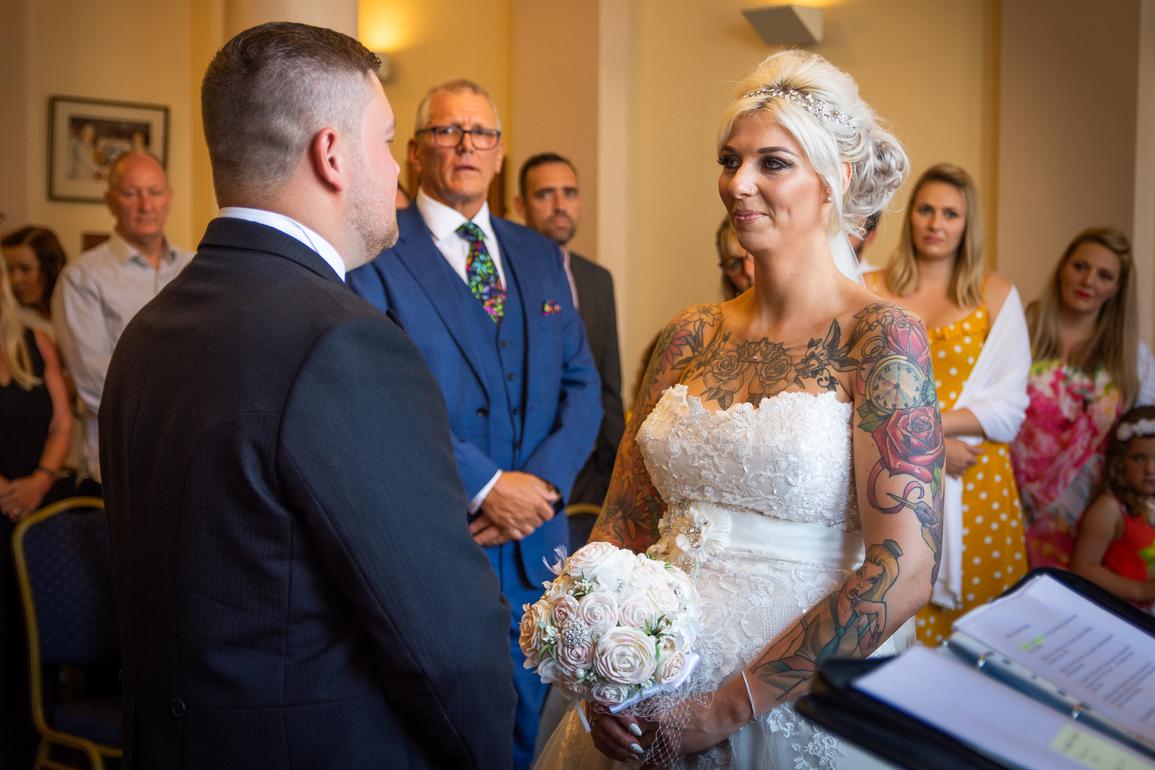 A couple are shown holding hands and looking at each other during their wedding ceremony at Hull Guildhall.