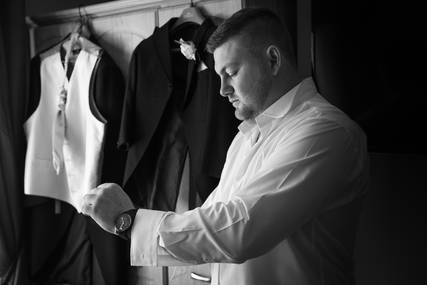 A groom puts in his cufflinks before the wedding ceremony.