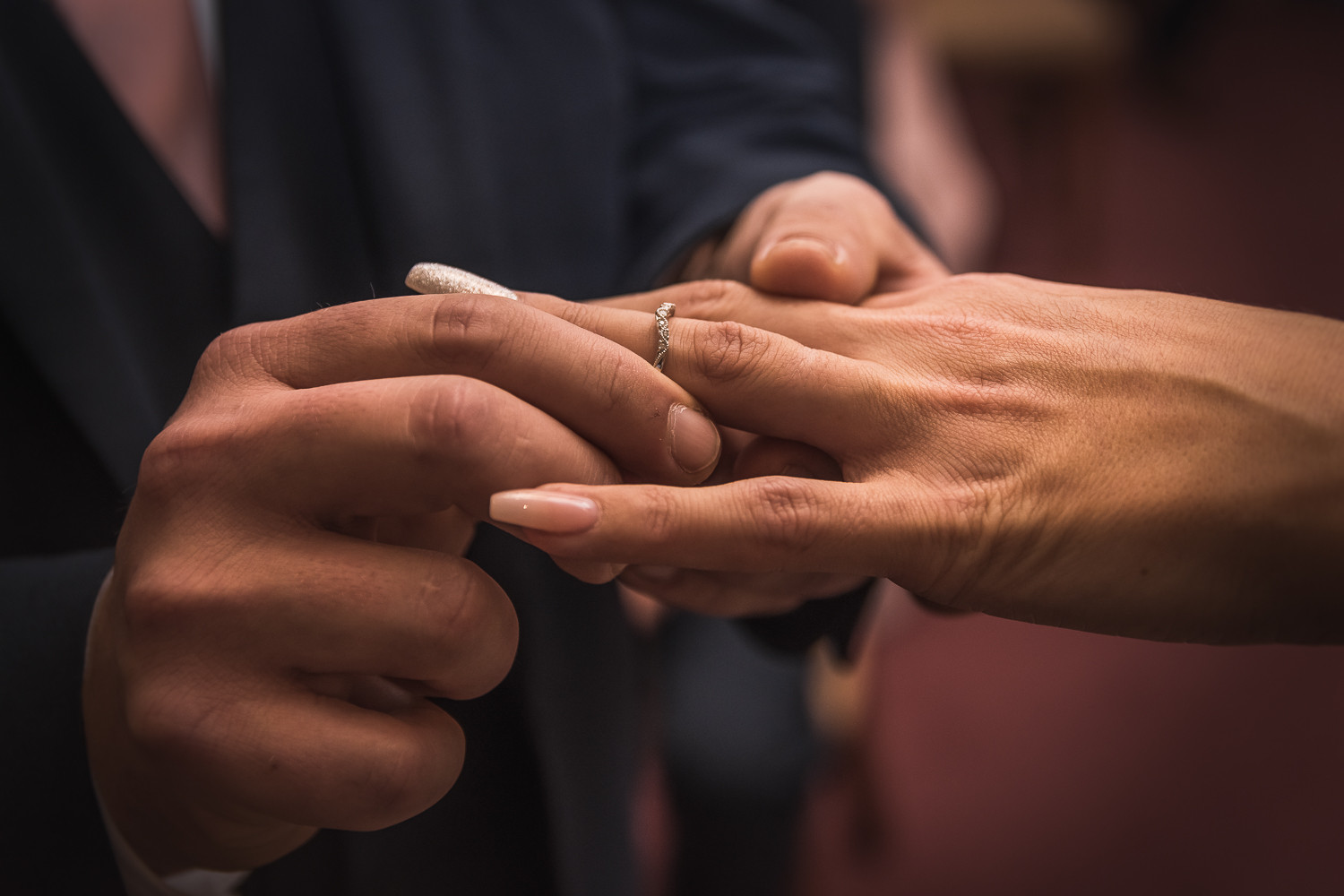 A groom places a bride's wedding ring on her hand during a wedding ceremony at Beverley Registry Office.