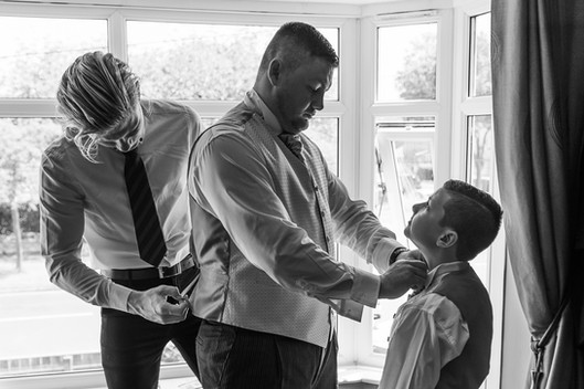 A groom, best man and page boy are shown helping each other prepare for a wedding.
