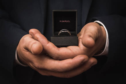 A detail photograph of two wedding rings in a case, being handled by the groom.