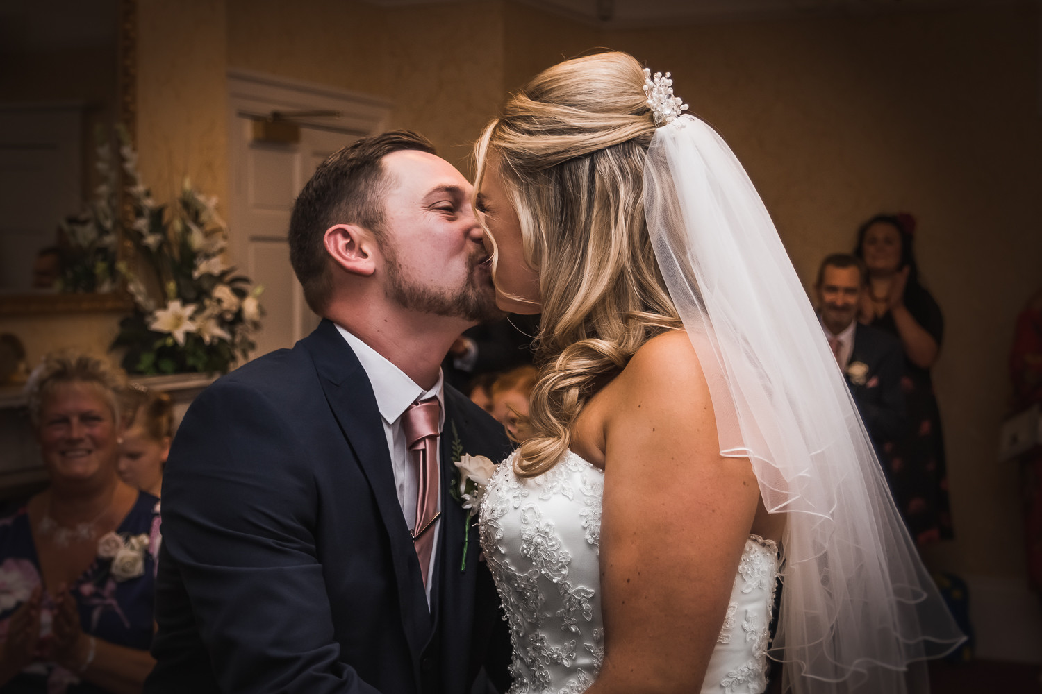A bride and groom kiss during their wedding ceremony.