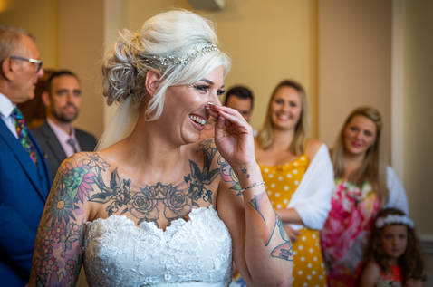 A bride with the giggles. She tries to cover her mouth with her hand.