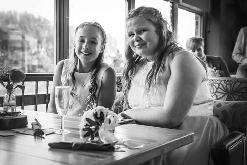 Two young wedding guests sit at the reception.
