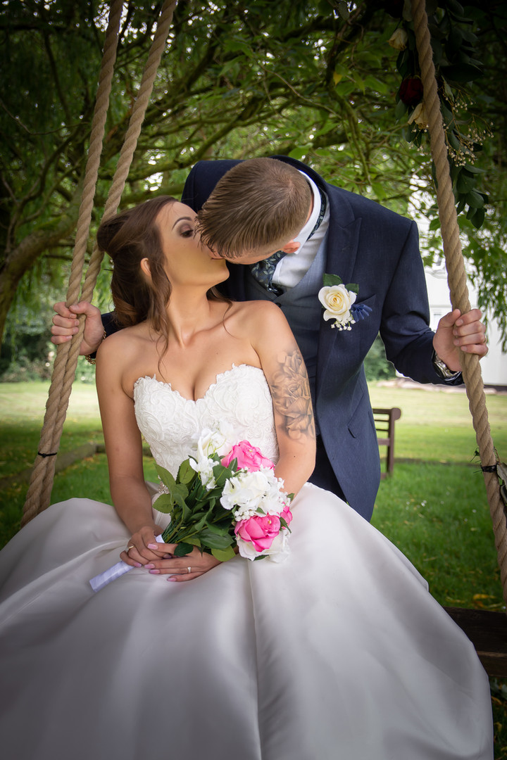 A bride sits on a swing, being pushed by the groom. She looks backwards and they kiss.