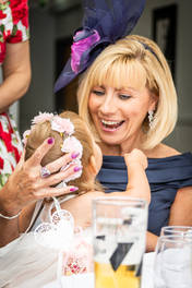 A wedding guest smiles at a baby at the reception.