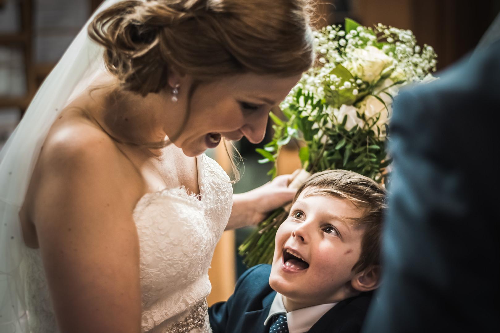 A young boy smiles gleefully at a bride.