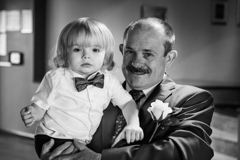 A young wedding guest and his grandfather smile for the camera.
