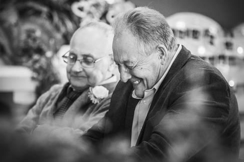 Two wedding guests enjoy a joke.