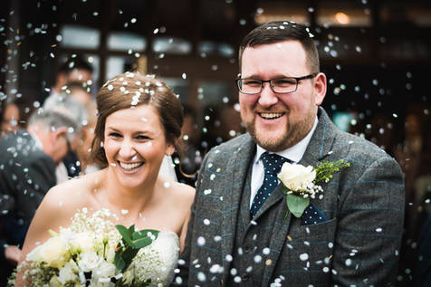 A newlywed bride and groom emerge from Willerby Methodist Church. They are covered in confetti.