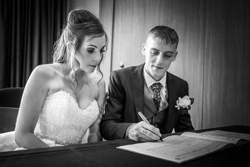 The bride and groom sign the register at the Hallmark Hotel near Hull.