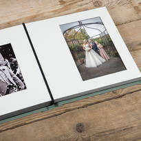 In this photograph an open wedding photography album is shown. The prominent photograph shows a bride, groom and child posing for a photograph after the wedding ceremony.