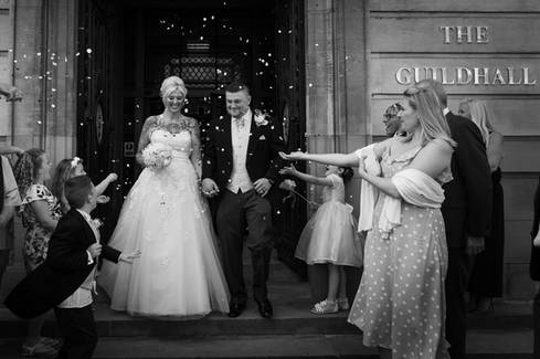 A bride and groom emerge from Hull Guildhall and are showered with confetti.