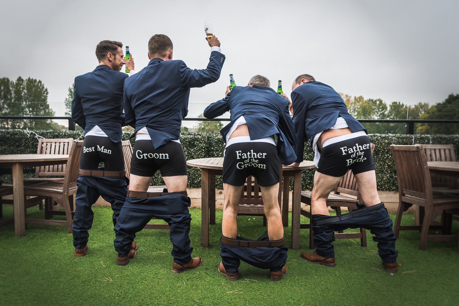 The groom, best man, and fathers of the bride and groom are photographed showing personalised, novelty underwear.