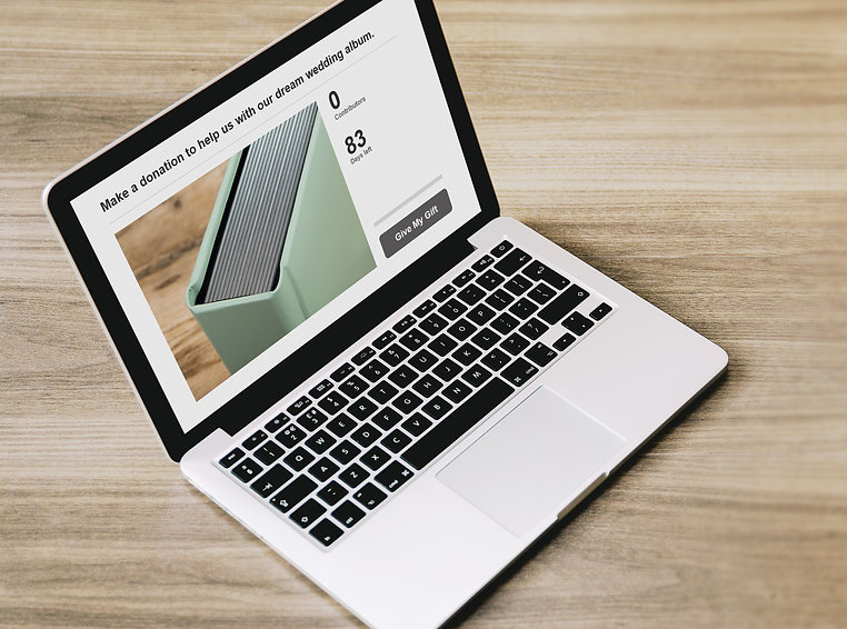 A laptop computer is shown open on a wooden surface. The screen shows a donation page towards the cost of a wedding photography album.