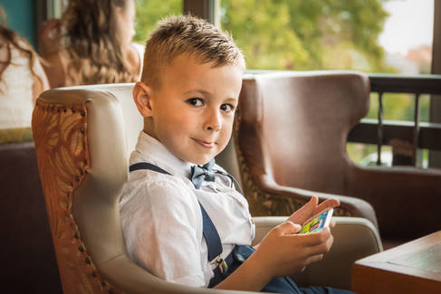 A young boy sits at the wedding recpetion, playing with a mobile phone.
