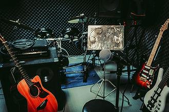 Salón de ensamble con guitarras, microfono, atriles, cables, batería