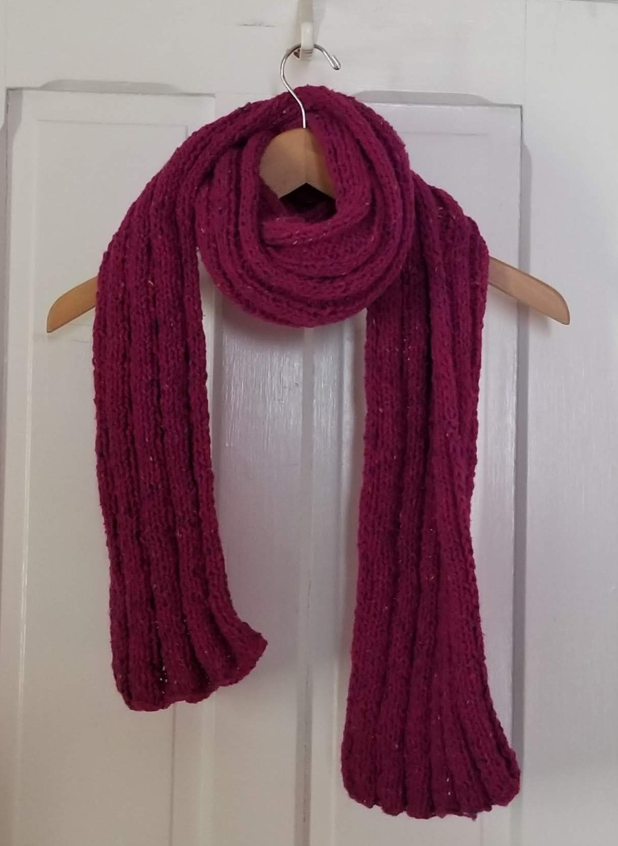 A hand knit magenta scarf.