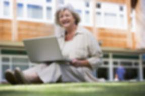 senior-using-laptop-on-college-campus-le