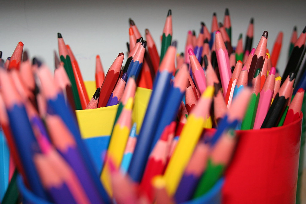 There are many colored pencils in pots, point-side up.