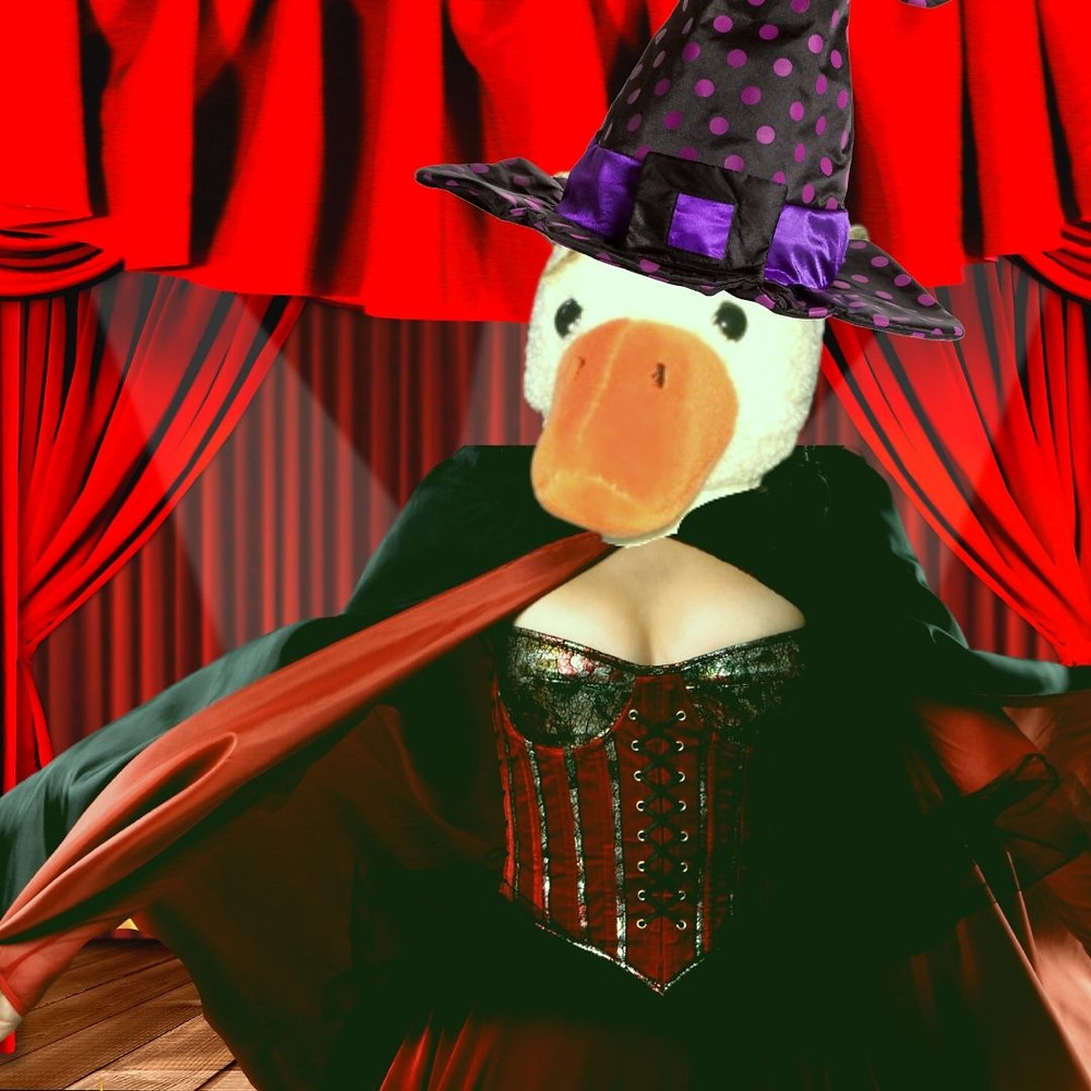 Duck is dressed in a witch's outfit, onstage. His outfit includes corset, with full cleavage that clearly belongs on a human).