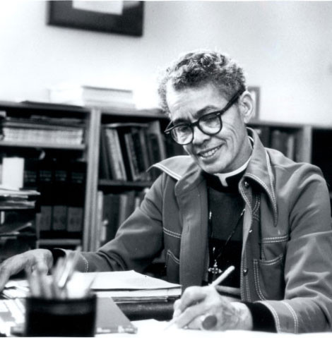 Dr. Pauli Murray writes at her desk, with bookshelves in the background. She is smiling.