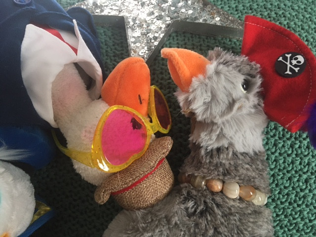 Duck and Goose Luce, both stuffies, are lounging together on a rug. Goose Luce wears a pirate hat and Duck wear's his suit and tie, plus a pair of heart-shaped sunglasses.