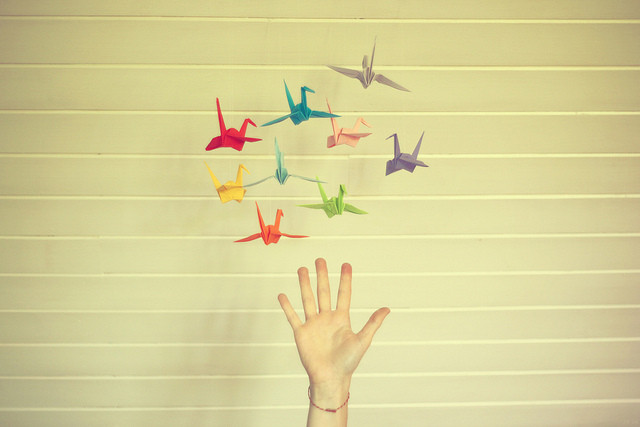 A hand releases origami birds into the air. They are multi-colored.
