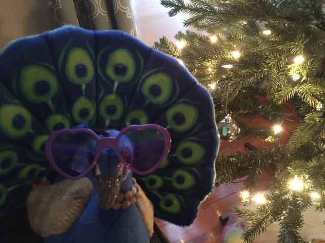 Peacock Riley wears their classic heart-shaped sunglasses in front of a Christmas tree with white lights and baubles.