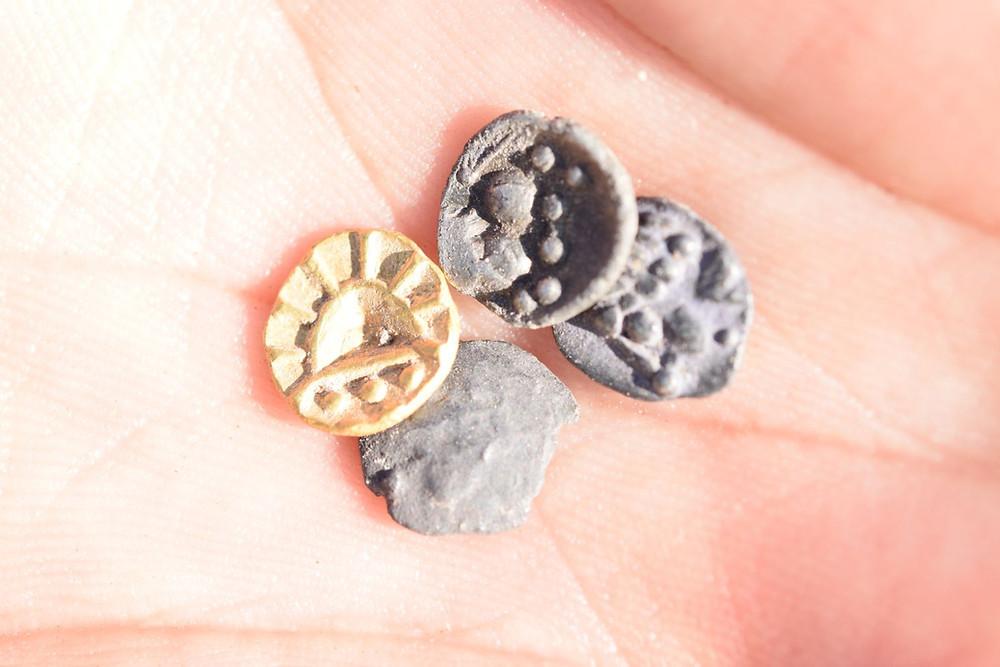 Drobné mince v dlani po nálezu. Foto M. Kratochvíl