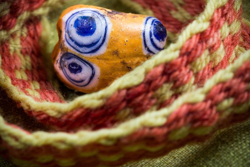 Skleněný korálek s očky, typický nález pro dobu halštatskou. Foto J. Lohnická