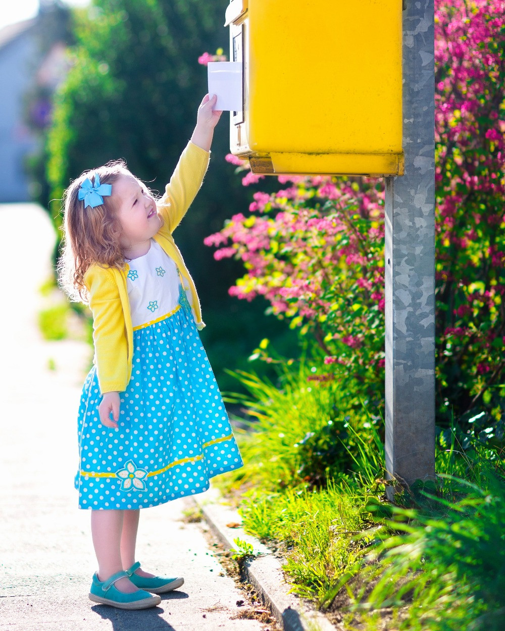 A little girl reaches up to put a letter into a tall, yellow mailbox on a sunny day.