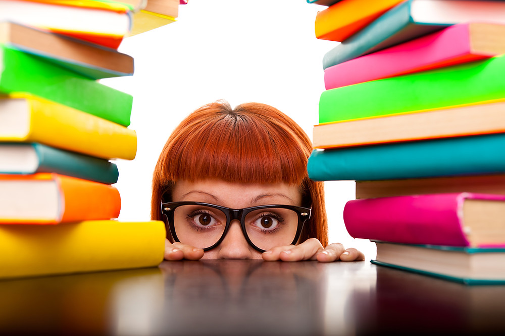 A girl peeks above a table surrounded with books