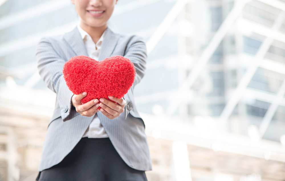 A woman in a grey suit holds out a red heart shaped pillow, as if offering it to the viewer.