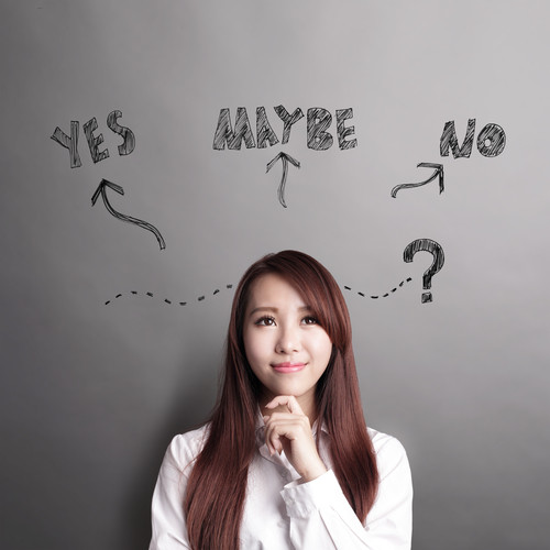 Woman looks thoughtful, behind her yes no and maybe are written on the wall