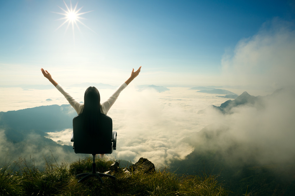 A girl embracing the sun sits on an office chair on the top of a mountain