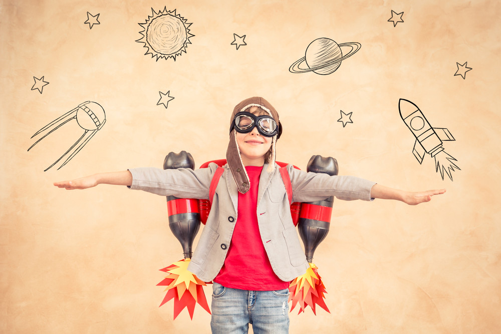 A child is wearing a homemade jet pack in front of a drawn planet background