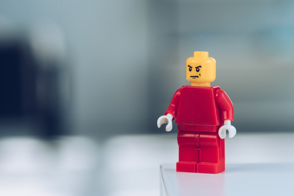 A small lego toy person in red stands on a countertop
