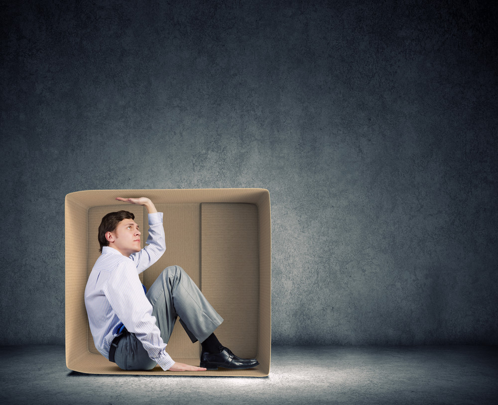 A man dressed in business attire sits in a large box and pushes on the top