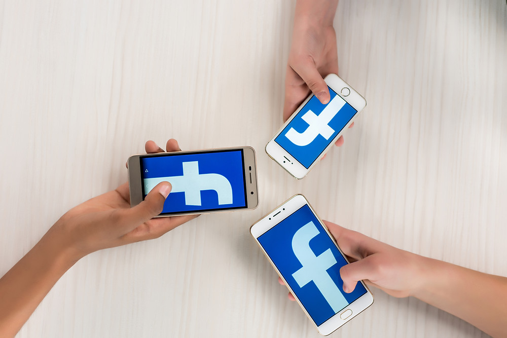 Three different hands hold a smartphone with the Facebook logo on the screen