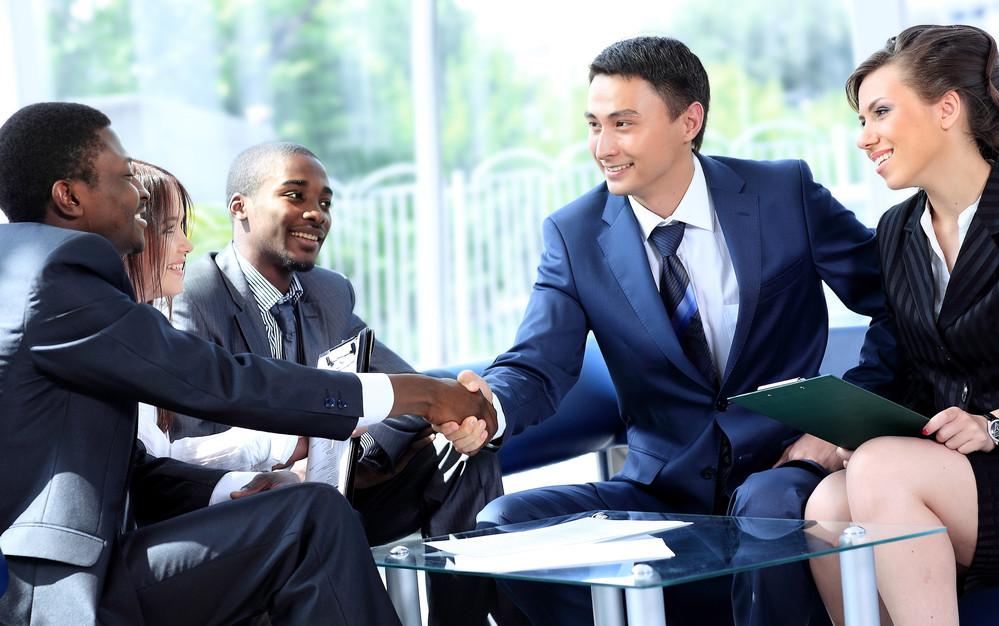 Corporate men and women in suits shake hands